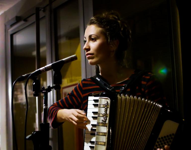 Camille, l'accordéoniste du trio musical Michel ou rien, lors du concert au Bar Commun dans le dix huitième arrondissement de Paris.